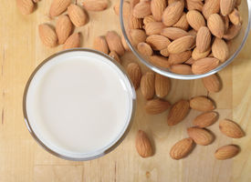 pic of substitutes  - Almond milk as a substitute for dairy milk. Glass of almond milk and almonds on a wooden table. ** Note: Shallow depth of field - JPG