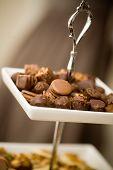 Chocolate pralines on white plate, very shallow focus