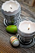 Easter candles on wooden table with egg decorations