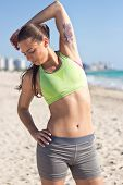 Girl Stretching On The Beach After A Workout