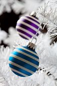 Colourful christmas baubles hanging from white christmas tree