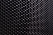Close up of a black gray protective speaker grille
