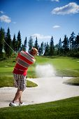 Male golfer shooting a golf ball from sand