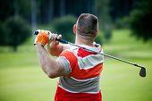 Male golfer shooting a golf ball from green grass
