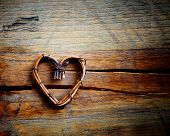Wooden background with willow heart, selective focus
