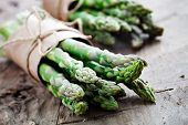 stock photo of ingredient  - Bunch of fresh asparagus on wooden table - JPG