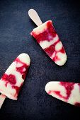 Homemade popsicles with vanilla pudding and raspberries