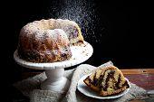 Marble bundt cake on wooden table, black background