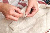 pic of thread-making  - Woman hands sewing with needle and thread - JPG