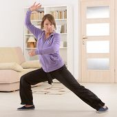 stock photo of qi  - Beautiful woman doing qi gong tai chi exercise at home - JPG