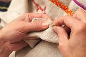 stock photo of thread-making  - Woman hands sewing with needle and thread close-up [[** Note: Shallow depth of field] ** Note: Visible grain at 100%, best at smaller sizes - JPG