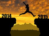 stock photo of happy new year 2014  - Girl jumps to the  New Year 2015  - JPG
