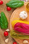 Colorful fettuccine pasta and cooking ingredients on wooden table
