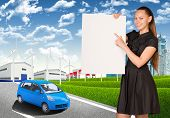 Businesswoman holding empty paper. Industrial zone, buildings and road with car
