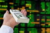 money in hand on stock exchange board background