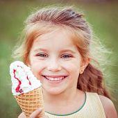 Beautiful little girl eats ice-cream in the summer