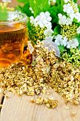 Tea from flowers of viburnum in strainer on board