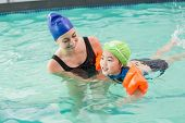 Cute little boy learning to swim with coach at the leisure center
