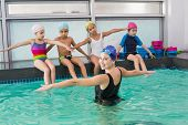 Cute swimming class watching the coach at the leisure center