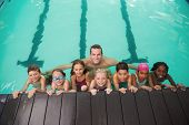 Cute swimming class in pool with coach at the leisure center