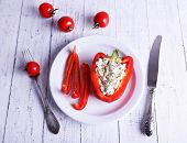 Stuffed pepper on plate and tomatoes on wooden background