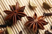 Stars anise with cardamom and carnation on wicker background