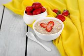 Tasty oatmeal with strawberry on table close-up