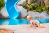 foto of crawling  - Cute little baby boy in a swimming diaper crawling at pool side having fun during summer vacation in a beautiful tropical resort - JPG