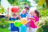 pic of little young child children girl toddler  - Happy big family young parents with three children teenager boy little toddler girl and adorable baby celebrating birthday party with strawberry cake and balloons in a sunny summer tropical garden - JPG
