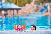 pic of floaties  - Two happy children adorable toddler girl and teenager boy brother and sister playing in a pool having fun enjoying family summer vacation in a beautiful tropical resort - JPG