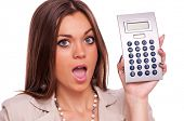 Surprised young business woman holding calculator - isolated on white