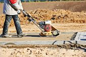 image of vibration plate  - builder worker at sand ground compaction with vibration plate compactor machine before pavement roadwork - JPG