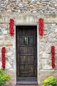 Hanging Chili Peppers Adorning A Stone Wall