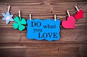 stock photo of four  - Blue TagWith Phrase Do What You Love On It Hanging on a Line with Different Symbols Like A Flower Four - JPG