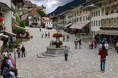 Central street of Gruyere in Switzerland with tourists.  Includes the town well and a cobbled square