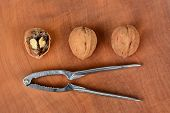 High angle shot of three walnuts and a nutcracker on a wood surface, one nut is cracked in half. Horizontal format.