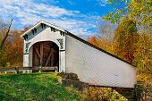 stock photo of foliage  - The Richland Creek Covered Bridge in rural Greene County Indiana is surrounded by colorful fall foliage on a sunny autumn day - JPG