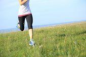 Runner athlete running on grass seaside. woman fitness jogging workout wellness concept.