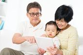 Asian family using digital tablet computer, grandparents and grandchild living lifestyle at home.