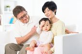 Asian family relaxing at home, grandparents and grandchild living lifestyle indoor.