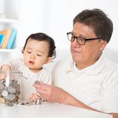 image of grandpa  - Asian family saving coins indoor - JPG