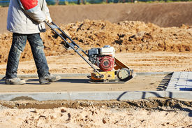 foto of vibration plate  - builder worker at sand ground compaction with vibration plate compactor machine before pavement roadwork - JPG