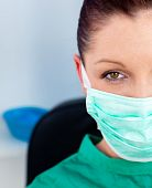 Close-up Of A Beautiful Female Doctor With Scrubs Sitting In Her Office