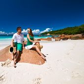 stock photo of couple sitting beach  - Couple in green sitting on a rock at tropical Seychelles beach - JPG