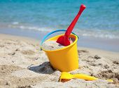 image of shovel  - Yellow sand pail and shovel on a beach - JPG