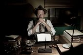 picture of 1950s  - 1950s journalist working late at night in his office typing on a typewriter - JPG