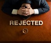 stock photo of rejection  - Word Rejected made of wooden block letters and devastated middle aged caucasian man in a black suit sitting at the table with the glass of whiskey - JPG