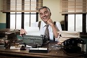 picture of 1950s style  - Smiling reporter working at office desk with vintage typewriter 1950s style.