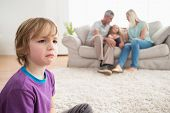 image of upset  - Upset boy sitting on floor while parents enjoying with sister on sofa at home - JPG