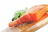 image of redfish  - single pink salmon bit on a big wooden dish with white cheese - JPG